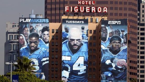 A three–paneled ad of the Playmakers adorns the side of Hotel Figueroa in downtown Los Angeles.
